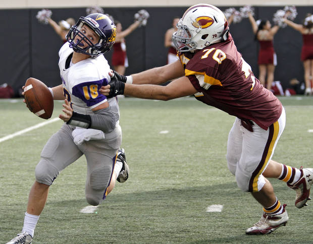 Anadarko's Brandon Pollard (18) tries to escape Clinton's Owen Poe (7) during the Class 4A Oklahoma state championship football game between Anadarko and Clinton at Boone Pickens Stadium on Saturday, Dec. 1, 2012, in Stillwater, Okla.   Photo by Chris Landsberger, The Oklahoman