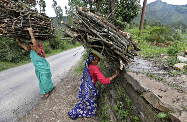 In this Aug. 25, 2012 photo, Devki Bisht, mother of Shoba Bisht who works at B2R, center, picks a up a load of firewood to use at home in Simayal, India. Devki insisted that her daughter Shoba be allowed to work when her son tried to talk her out of it, and now Shoba has helped the family by providing money for building additional rooms as well as her brother's hospital bills. (AP Photo/Saurabh Das)
