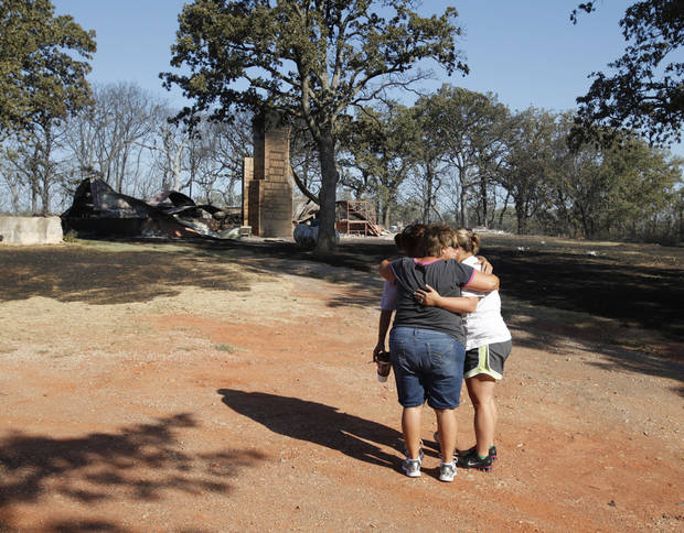 The Grigg family hugs Saturday as they gather to see for the first time the damage from Friday�s wildfire in Slaughterville. Photo by Steve Sisney, The Oklahoman