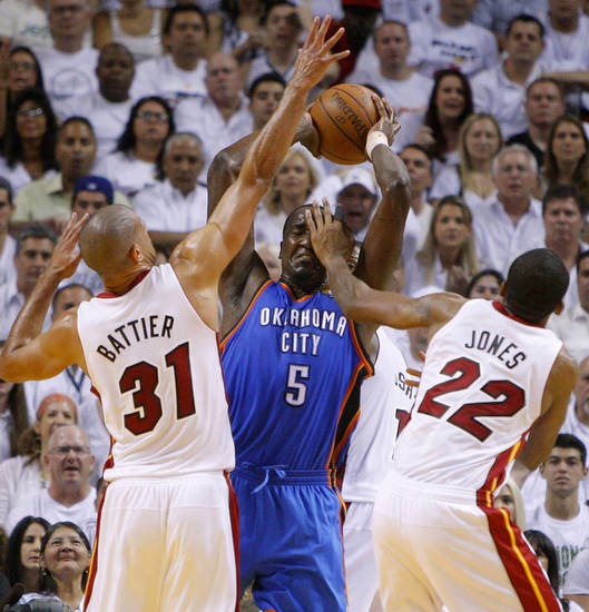 Oklahoma City's Kendrick Perkins (5) grabs the ball between Miami's Shane Battier (31) and James Jones (22) during Game 3 of the NBA Finals between the Oklahoma City Thunder and the Miami Heat at American Airlines Arena, Sunday, June 17, 2012. Photo by Bryan Terry, The Oklahoman