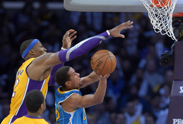 Los Angeles Lakers center Dwight Howard, left, blocks the shot of New Orleans Hornets guard Brian Roberts during the second half of their NBA basketball game, Tuesday, Jan. 29, 2013, in Los Angeles. The Lakers won 111-106. (AP Photo/Mark J. Terrill)