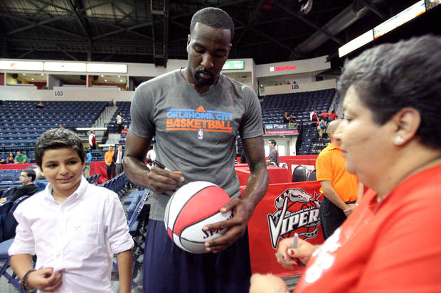 Oklahoma City Thunder's Serge Ibaka, center, of the Republic of Congo, autographs a basketball for fans before the start of their preseason NBA basketball game against the Houston Rockers, Wednesday, Oct. 10, 2012, in Hidalgo, Texas. (AP Photo/Delcia Lopez) ORG XMIT: TXDL101