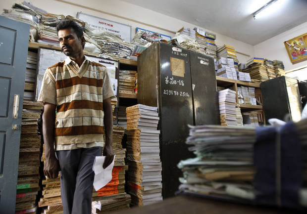 In this Dec. 10, 2012 photo, a man stands amid piles of documents of land records inside a room at the government registrar's office in Hoskote 30 Kilometers (19 miles) from Bangalore in southern Indian state of Karnataka.  For years, Karnataka's land records were a quagmire of disputed, forged documents maintained by thousands of tyrannical bureaucrats who demanded bribes to do their jobs. In 2002, there were hopes that this was about to change. (AP Photo/Aijaz Rahi)