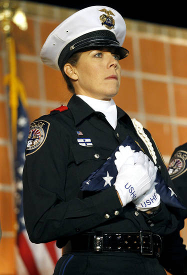 A Midland police officer holds the U.S. Honor Flag during a candlelight vigil held Saturday, Nov. 17, 2012 at Centennial Plaza in Midland, Texas in honor of the veterans who were killed when a freight train hit a parade float Thursday. The Honor Flag was originally dedicated in memory of those killed during the 9/11 terrorist attacks and has since been around the world and even into space in honor of American heroes who have lost their lives. (AP Photo/Midland Reporter-Telegram, James Durbin)