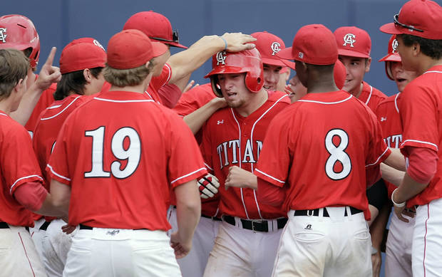 Titans catcher Taylor Hawkins (center) collects congrats from teamates after his home run against the Zebras during their 5A State Baseball Championship at Oral Roberts University in Tulsa, OK, May 12, 2012. MICHAEL WYKE/Tulsa World