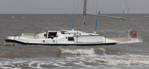 Waves crash on a beached sailboat in Gulf Port , Miss.,  Tuesday, Aug. 28, 2012.  The U.S. National Hurricane Center in Miami said Isaac became a Category 1 hurricane Tuesday with winds of 75 mph. It could get stronger by the time it's expected to reach the swampy coast of southeast Louisiana. (AP Photo/John Bazemore) ORG XMIT: MSJB104