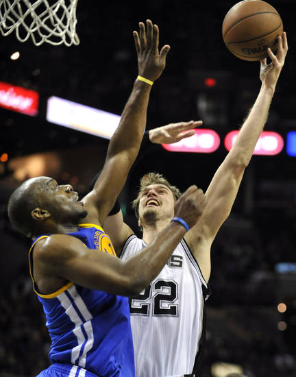 San Antonio Spurs forward Tiago Splitter (22), of Brazil, shoots over Golden State Warriors forward Carl Landry, left, during the first half of an NBA basketball game on Friday, Jan. 18, 2013, in San Antonio. (AP Photo/Bahram Mark Sobhani)