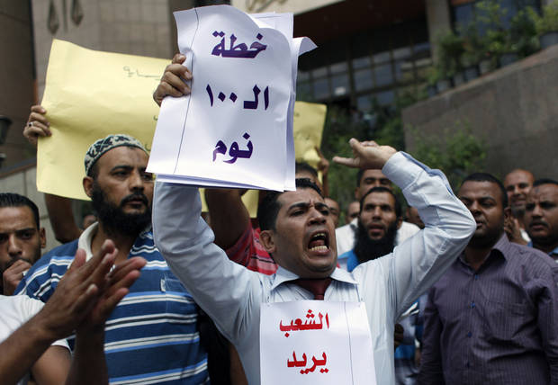 "An Egyptian protester carries placards that read in Arabic ""the 100 sleeping days plan"" and, partially shown, ""the people wants to dissolve the constituent assembly,"" and chants slogans against the constituent assembly, an Islamists dominated panel writing Egypt's new constitution, during a protest in front of the State Council's headquarters in Cairo, Egypt, Tuesday, Oct. 9, 2012. Human Rights Watch on Monday urged the panel writing Egypt's new constitution to amend articles in the draft that the New York-based group says repress the rights of women and children and limit freedom of religion and expression. (AP Photo/Nasser Nasser)"