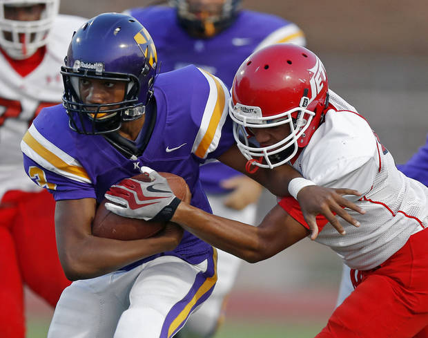 Northwest Classen's Jalen Harris runs past Western Heights' Davonte Drennan during a high school football game at Taft Stadium in Oklahoma City, Thursday, September 20, 2012. Photo by Bryan Terry, The Oklahoman