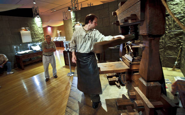 Andrew Cole demonstrates the operations of a Gutenberg press to visitors of the �Passages� exhibit at the Oklahoma City Museum of Art. The collection of biblical artifacts was on display last year. Photos by Chris Landsberger, The Oklahoman Archives