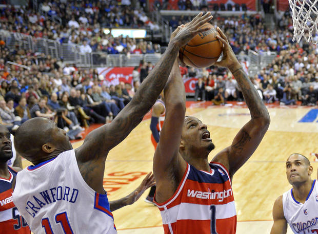 Washington Wizards forward Trevor Ariza, center, puts up a shot as Los Angeles Clippers guard Jamal Crawford, left, defends and forward Grant Hill watches during the first half of their NBA basketball game, Saturday, Jan. 19, 2013, in Los Angeles.  (AP Photo/Mark J. Terrill)