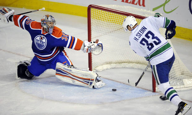 Vancouver Canucks' Henrik Sedin (33) scores on Edmonton Oilers goalie Nikolai Khabibulin during the first period of an NHL hockey game in Edmonton, Alberta, Sunday, Feb. 19, 2012. (AP Photo/The Canadian Press, John Ulan)