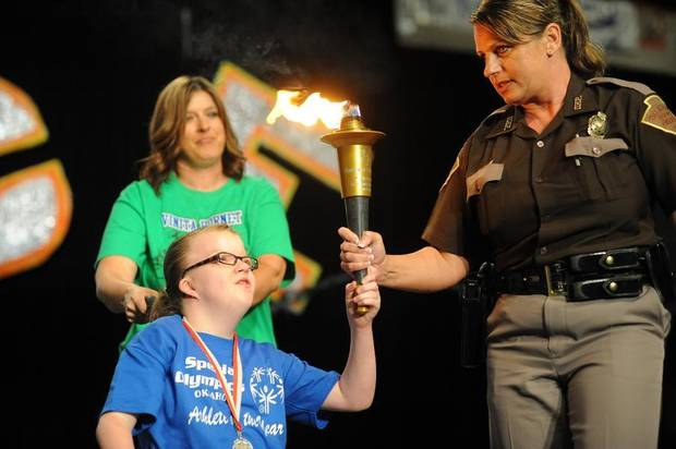 2013 Special Olympics Oklahoma Athlete of the Year Lyndsey Streeter, of Vinita, assists the Tim Stafford Unsung Hero Memorial Award winner, Oklahoma Highway Patrol trooper Jennifer Fisher, in holding the ceremonial torch during open ceremonies. (Stillwater NewsPress photo)