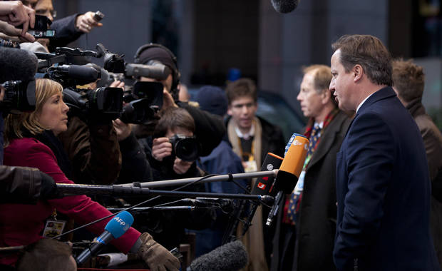 British Prime Minister David Cameron, right, speaks with the media as he arrives for an EU summit in Brussels on Thursday, Dec. 13, 2012. In one whirlwind morning, the European Union nations agreed on the foundation of a fully-fledged banking union and Greece�s euro partners approved billions of euros in bailout loans that will prevent the nation from going bankrupt. (AP Photo/Virginia Mayo)