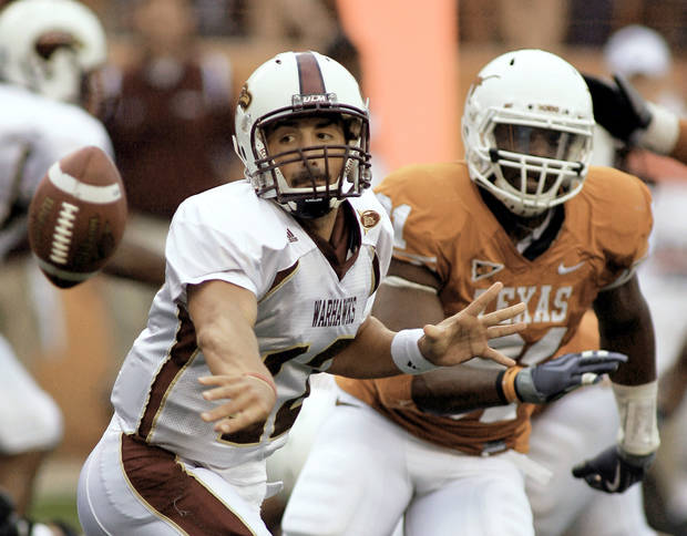 Texas defensive end Sam Acho, right, defends as Louisiana-Monroe quarterback Trey Revell pitches out during first-quarter action Saturday. AP Photo