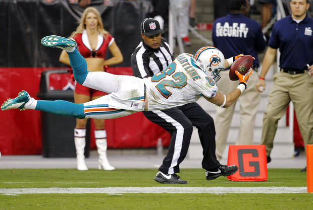 CORRECTS TO TOUCHDOWN, NOT SET UP FOR A TOUCHDOWN - Miami Dolphins wide receiver Brian Hartline (82) dives for the end zone to score a touchdown during the second half of an NFL football game against the Arizona Cardinals, Sunday, Sept. 30, 2012, in Glendale, Ariz. (AP Photo/Matt York)