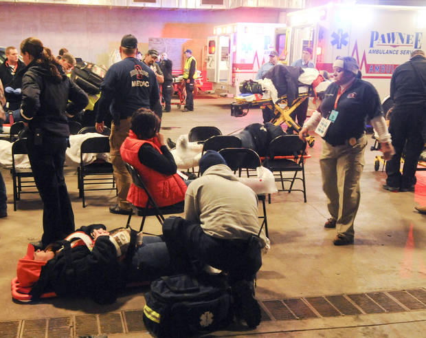 Emergency medical personnel tend to injured fans under Boone Pickens Stadium following Oklahoma State's 44-10 win over rival Oklahoma in an NCAA college football game in Stillwater, Okla., Saturday, Dec. 3, 2011. Fans were injured during the course of celebrating, which included running onto the field and tearing down goal posts. (AP Photo/Brody Schmidt) ORG XMIT: OKBS109