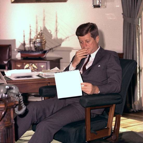 In this Jan. 18, 1962 file photo, U.S. President John F. Kennedy looks over notes at his desk in the White House. (AP Photo/Henry Burroughs)