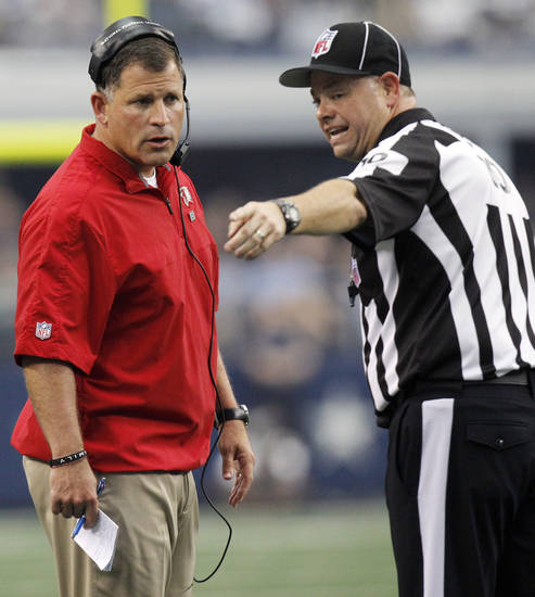 Head Linesman Wayne Bernier (10) talks with Tampa Bay Buccaneers head coach Greg Schiano during the first half of an NFL football game against the Dallas Cowboys, Sunday, Sept. 23, 2012, in Arlington, Texas. (AP Photo/LM Otero)