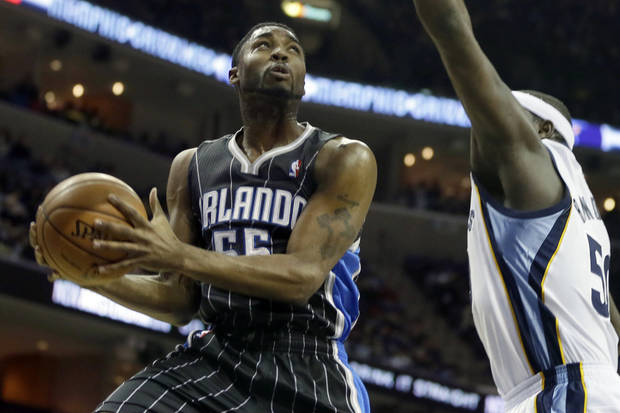 Orlando Magic's E'Twaun Moore (55) goes to the basket in front of Memphis Grizzlies' Zach Randolph during the first half of an NBA basketball game in Memphis, Tenn., Friday, Feb. 22, 2013. (AP Photo/Danny Johnston)