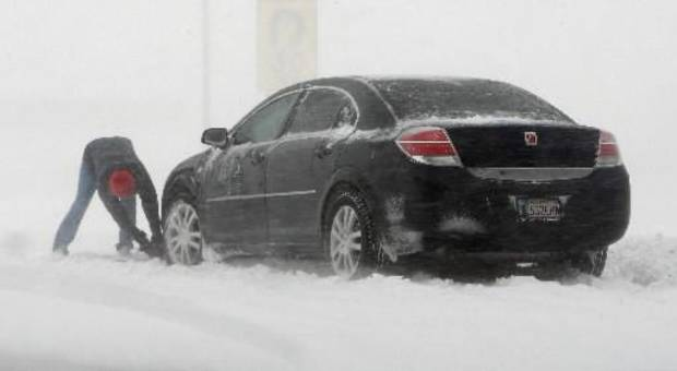 A motorist tries to free their car stuck in a snow drift in the southbound lanes of SH 81 just south of I-40 in El Reno Thursday, Dec. 24, 2009. Photo by  Paul B.  Southerland