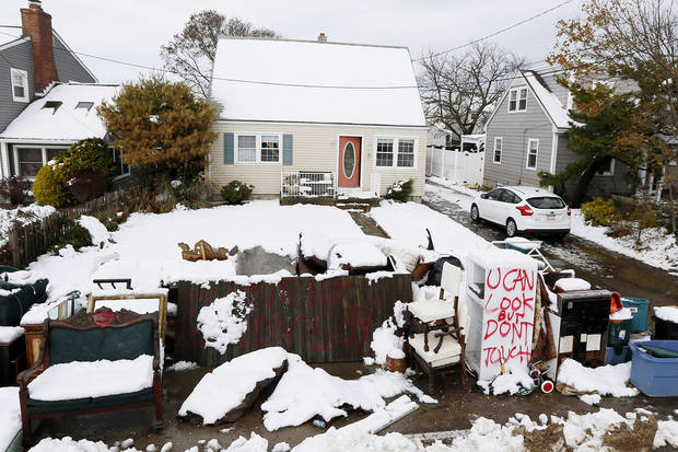 Messages are written on snow covered debris from Superstorm Sandy outside of the Miller residence following a nor'easter storm, Thursday, Nov. 8, 2012, in Point Pleasant, N.J.  The New York-New Jersey region woke up to wet snow and more power outages Thursday after the nor'easter pushed back efforts to recover from Superstorm Sandy, that left millions powerless and dozens dead last week. (AP Photo/Julio Cortez) ORG XMIT: NJJC119