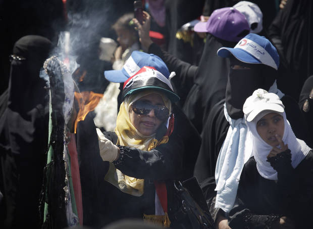 A female Yemeni  protestor burns veils during a demonstration demanding the resignation of Yemeni President Ali Abdullah Saleh in Sanaa, Yemen, Wednesday, Oct. 26, 2011. The burning of the veil was not related to women's rights or issues surrounding the Islamic veils - rather, the act of women burning their clothing is a symbolic Bedouin tribal gesture signifying an appeal for help to tribesmen, in this case to stop the attacks on women protesters. (AP Photo/Hani Mohammed) ORG XMIT: CAI111
