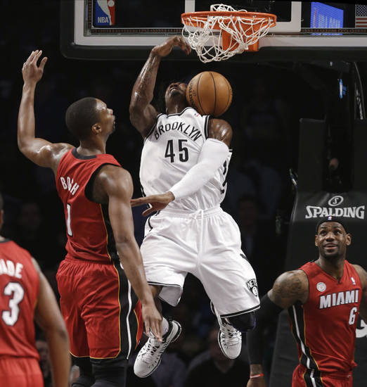 Brooklyn Nets forward Gerald Wallace (45) dunks between Miami Heat center Chris Bosh (1) and forward LeBron James (6) during the first half of an NBA basketball game Wednesday, Jan. 30, 2013, in New York. (AP Photo/Kathy Willens)