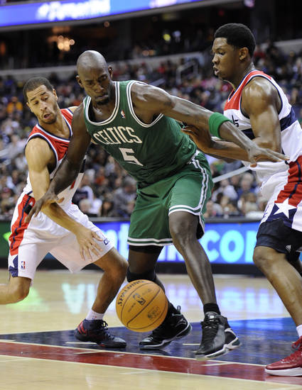 Boston Celtics forward Kevin Garnett, center, battles for the ball against Washington Wizards guard Jannero Pargo, left, and Kevin Seraphin, right, of France, during the first half of an NBA basketball game on Saturday, Nov. 3, 2012, in Washington. (AP Photo/Nick Wass)