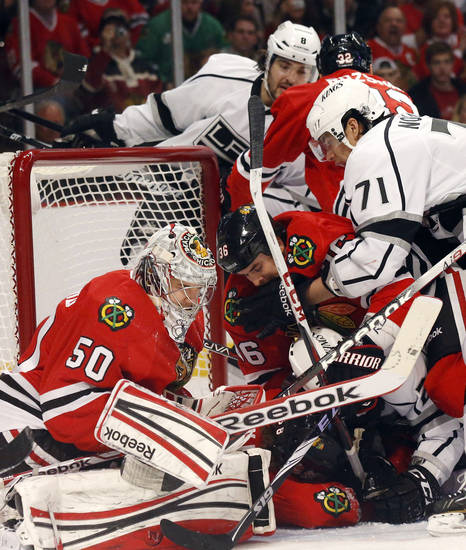 Several Chicago Blackhawks and Los Angeles Kings players crash into the goal crease near goalie Corey Crawford during the first period of an NHL hockey game, Monday, March 25, 2013, in Chicago. (AP Photo/Charles Rex Arbogast)