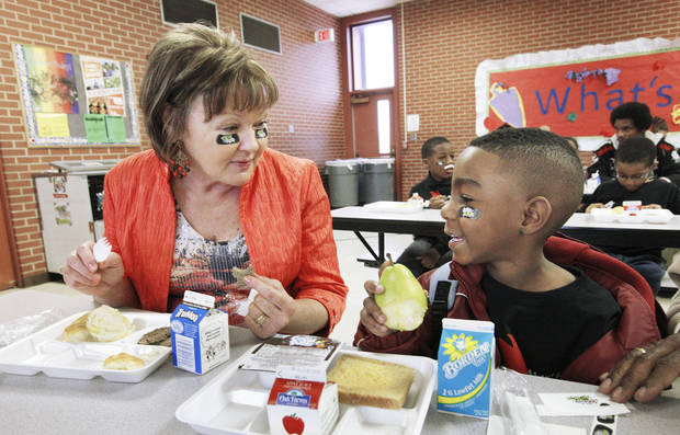 Right: Wearing NFL Play 60 stickers under their eyes, Jamey Allen, Oklahoma Department of Agriculture market development director, eats breakfast with kindergarten student Ashton Butler, 6, during a National School Breakfast Week event at Pleasant Hill Elementary.