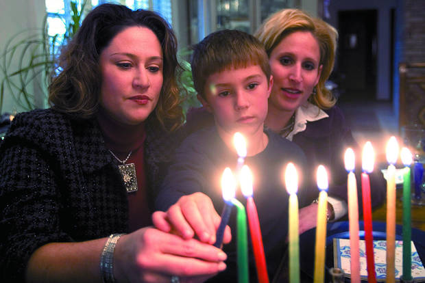 Barbie Greer, Jake Greer, 6, and Diane Barton light a menorah candle. PHOTO BY SARAH PHIPPS. THE OKLAHOMAN