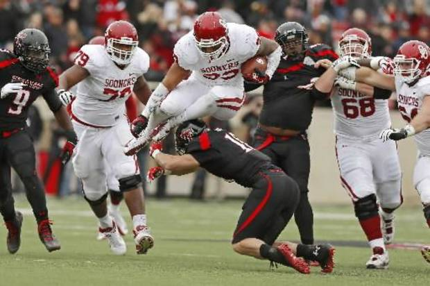 Oklahoma's Trey Millard (33) leaps over Texas Tech's Cody Davis (16) on Saturday, Oct. 6, 2012. Photo by Bryan Terry, The Oklahoman