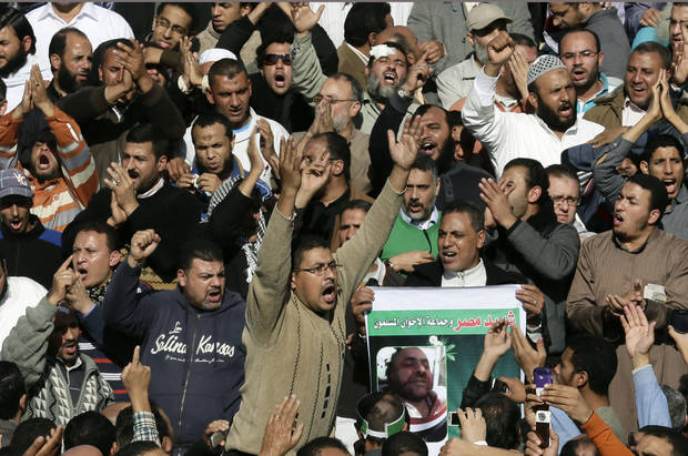 "Supporters of the Muslim Brotherhood and Egyptian President Mohammed Morsi, chant slogans during the funeral of three victims who were killed during Wednesday's clashes outside Al Azhar mosque, the highest Islamic Sunni institution, Friday, Dec. 7, 2012. During the funeral, thousands Islamist mourners chanted, ""with blood and soul, we redeem Islam,"" pumping their fists in the air. ""Egypt is Islamic, it will not be secular, it will not be liberal,"" they chanted as they walked in a funeral procession that filled streets around Al-Azhar mosque. (AP Photo/Hassan Ammar)"