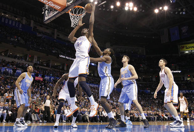 Oklahoma City's Hasheem Thabeet (34) goes to the basket past Denver's Kenneth Faried (35) during the NBA basketball game between the Oklahoma City Thunder and the Denver Nuggets at the Chesapeake Energy Arena on Wednesday, Jan. 16, 2013, in Oklahoma City, Okla.  Photo by Chris Landsberger, The Oklahoman