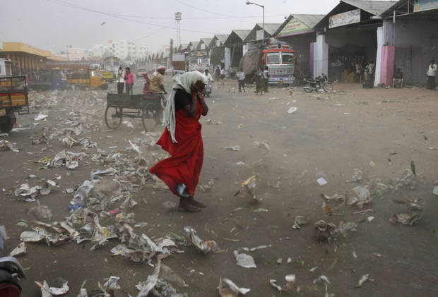 An Indian woman tries to shield herself from the wind in Hyderabad, India, Tuesday, April 2, 2013. (AP Photo/Mahesh Kumar A.)