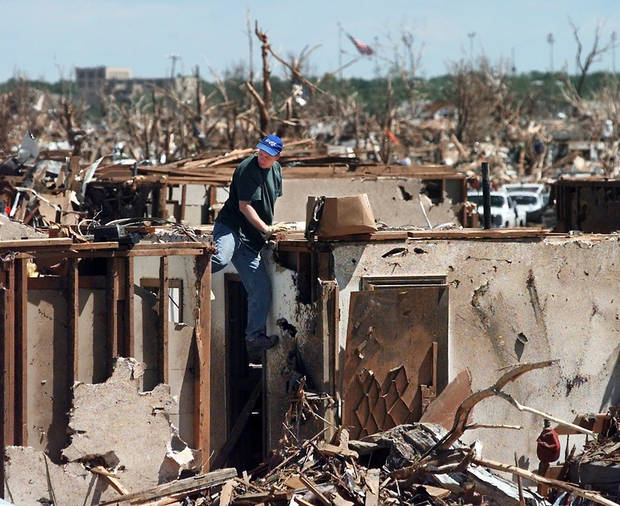 MAY 3, 1999 TORNADO: Tornado damage: An unidentified man climbs down from the ceiling rafters in a home that was destroyed in Monday night's tornado.  The home is in the Del Aire addition  north of SE 44th street in Del City.