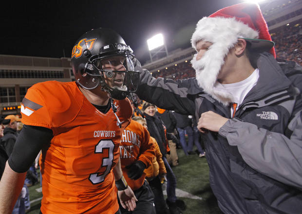 Fans celebrate with Oklahoma State&#039;s Brandon Weeden (3) after the Cowboys&#039; 44-10 win over Oklahoma during the Bedlam college football game between the Oklahoma State University Cowboys (OSU) and the University of Oklahoma Sooners (OU) at Boone Pickens Stadium in Stillwater, Okla., Saturday, Dec. 3, 2011. Photo by Chris Landsberger, The Oklahoman