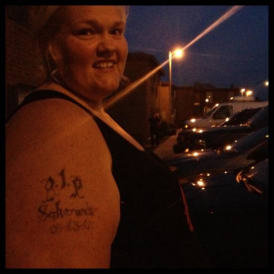 A woman at the June 7, 2013 homicide scene in Oklahoma City. The tattoo is for her mother, who died a year ago Mother's Day.