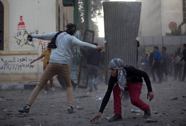 Egyptian protesters clash with riot police, not seen, near Tahrir Square, Cairo, Egypt, Friday, Jan. 25, 2013. Two years after Egypt's revolution began, the country's schism was on display Friday as the mainly liberal and secular opposition held rallies saying the goals of the pro-democracy uprising have not been met and denouncing Islamist President Mohammed Morsi. With the anniversary, Egypt is definitively in the new phase of its upheaval. (AP Photo/Khalil Hamra) ORG XMIT: KH132