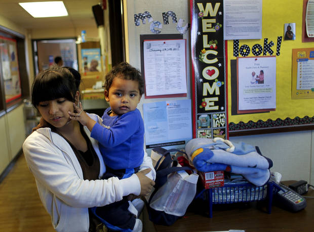 Emerson High School senior Julie Adame spends time with her 18-month-old son Xavier Patterson between classes while she visits him in the Head Start day care program at the school on Wednesday, Jan. 12, 2011, in Oklahoma City, Okla. The program offers young mothers a chance to get an education as well as their children.   Photo by Chris Landsberger, The Oklahoman