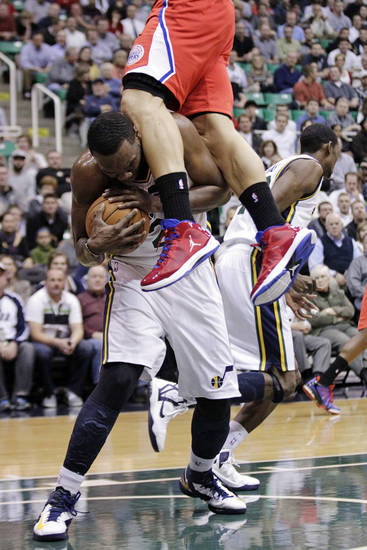 Los Angeles Clippers power forward Blake Griffin, top, fouls Utah Jazz center Al Jefferson (25) after Jefferson grabbed a rebound in the first quarter of an NBA basketball game, Monday, Dec. 3, 2012, in Salt Lake City. (AP Photo/Rick Bowmer)