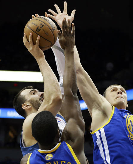 Minnesota Timberwolves' Nikola Pekovic of Montenegro, left, is double teamed by Golden State Warriors' Harrison Barnes and Andris Biedrins of Latvia, right, as he attempts a shot in the first quarter of an NBA basketball game Sunday, Feb. 24, 2013, in Minneapolis. (AP Photo/Jim Mone)