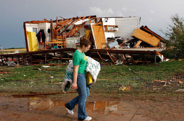 Rebecca Apel, 15,carries a blanket she retrieved from the rubble of her family's home and walks to a nearby van where salvageable belongings were placed.  Her home on SH 74 near Cashion was ripped apart by a tornado lateTuesday afternoon,  May 24, 2011,   No one was inside the house and there were no injuries. Photo by Jim Beckel, The Oklahoman