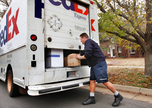 Longtime FedEx driver Ray Beltrane pulls a box  from the back of his truck as he makes a stop on N. McKinley to deliver packages to a home in Oklahoma City on Monday,  Dec. 12, 2011.    Photo by Jim Beckel, The Oklahoman