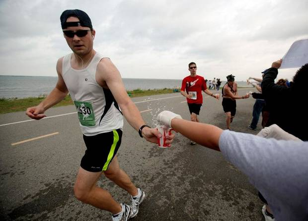 A runner grabs water at Lake Hefner during the Memorial Marathon, Sunday, April 26, 2009, in Oklahoma City.  Photo by Sarah Phipps, The Oklahoman