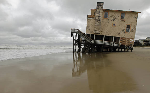 An abandoned beach house that survived the storm surge from Hurricane Sandy sits off center in Nags Head, N.C., Monday, Oct. 29, 2012. The storm continued on its path Monday, forcing  the shutdown of mass transit, schools and financial markets,  and sending coastal residents fleeing. (AP Photo/Gerry Broome) ORG XMIT: NCGB123