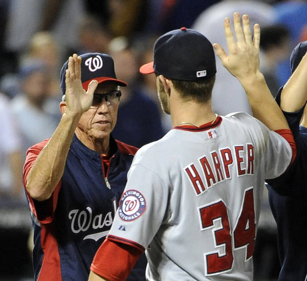 "FILE - In this July 24, 2012 file photo, Washington Nationals manager Davey Johnson high-fives Bryce Harper (34) after the Nationals defeated the New York Mets in a baseball game, at Citi Field in New York. One's the oldest manager in the majors. The other put together the best season by a teen hitter since the 1960s. Davey Johnson, 69, and Bryce Harper, 19, were born a half-century apart, and they came together to help the Washington Nationals build the best record in baseball in 2012. ""He's really not a kid; he's a man,"" Johnson says. ""But he's a kid to me."" (AP Photo/Kathy Kmonicek, File)"