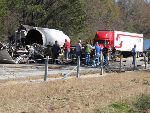 Crews work to clean up wreckage on Interstate 16 in middle Georgia, hours after 27 vehicles collided Wednesday, Feb. 6, 2013 near Montrose, Ga. More than two dozen cars, pickup trucks and tractor-trailers collided Wednesday morning in a fiery pileup on a foggy Georgia interstate 16, killing at least three people and sending nine others to a hospital, officials said. (AP Photyo/Russ Bynum)