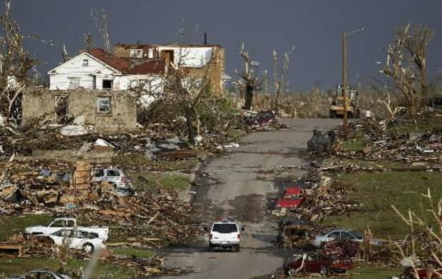 An emergency vehicle drives through a severely damaged neighborhood in Joplin, Mo., Monday, May 23, 2011. A large tornado moved through much of the city Sunday, damaging a hospital and hundreds of homes and businesses and killing at least 89 people. (AP Photo/Charlie Riedel)
